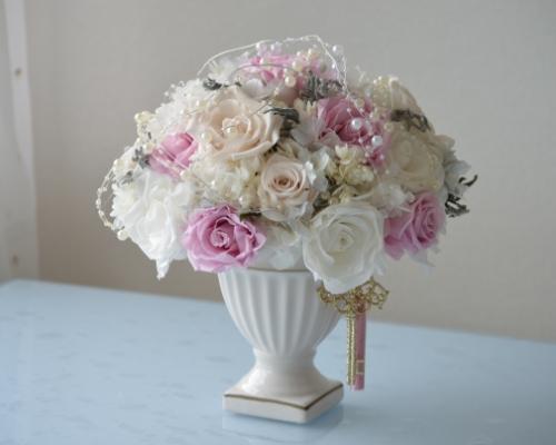 ロマンティックな甘いベールトーンのたくさんのプリザーブドフラワーをパール色の陶器の花器にふんわりとアレンジ
