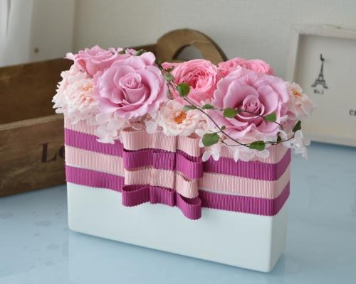 リボンをまとった白系のセラミックの花器にピンク色のプリザーブドフラワーのバラをアレンジ
