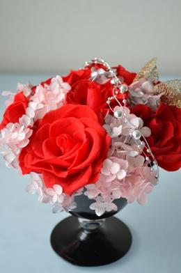 黒いガラスの花器に目の覚めるような赤色で大振りのプリザーブドフラワーのバラをアレンジ