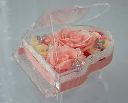 アクリル製のグランドピアノにピンクや白色のプリザーブドフラワーのバラをアレンジ
