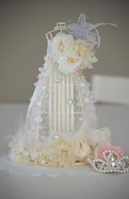白色のウェディングドレスをまとったドールにプリザーブドフラワーの花々をアレンジ