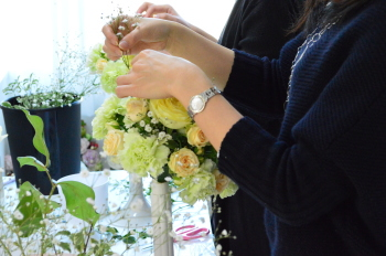 花嫁のためのラウンドブーケ(フレッシュフラワーアレンジメント)の製作、大きなお花とお花の間に小さなお花を挿していきます